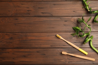 Flat lay composition with bamboo toothbrushes and space for text on wooden background