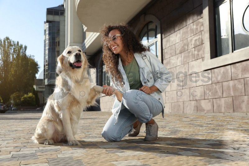 Young African-American woman and her Golden Retriever dog outdoors