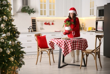 Young woman setting table for Christmas dinner in kitchen
