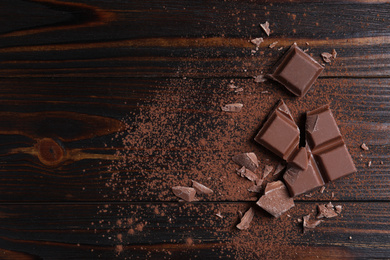 Delicious milk chocolate and cocoa powder on wooden table, flat lay. Space for text