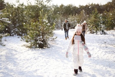 Cute little girl with her parents outdoors on winter day. Christmas vacation