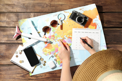 Woman marking calendar at table with world map, top view. Travel during summer vacation