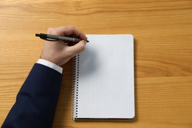 Left-handed man writing in notebook at wooden desk, top view