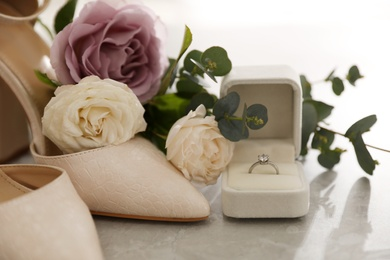 Wedding composition with engagement ring on light grey marble table, closeup. Bride dressing