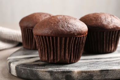 Delicious fresh chocolate cupcakes on grey marble board, closeup