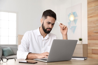 Handsome young man working with laptop at table in home office