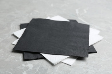 Clean napkins on grey marble table, closeup. Personal hygiene