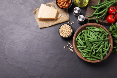 Fresh green beans and other ingredients on black table, flat lay. Space for text