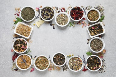 Frame of different dry teas on light grey table, flat lay. Space for text