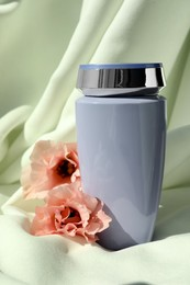 Bottle of hair care cosmetic product and beautiful flowers on light green fabric