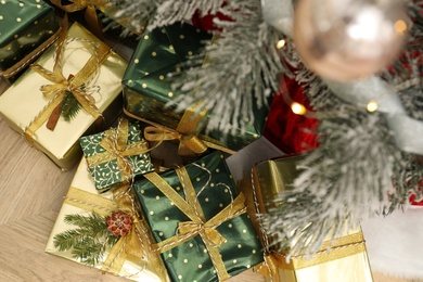 Many different gifts under Christmas tree indoors, top view