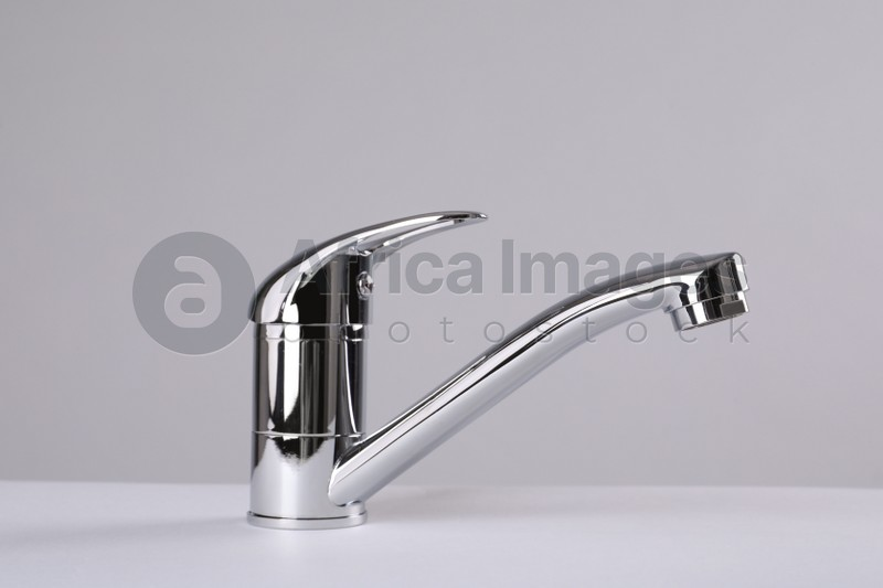 Single handle water tap on grey background