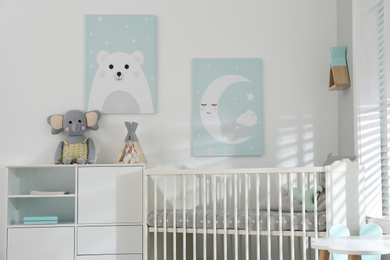 Stylish baby room interior with crib and cute wall art