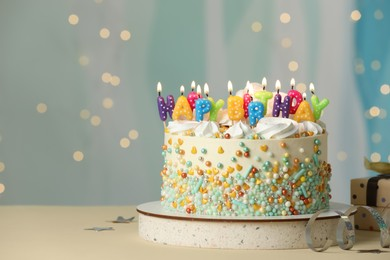 Beautiful birthday cake with burning candles and decor on white table. Space for text