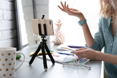 Female blogger recording video at table