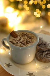 Tasty hot drink, cookies and Christmas lights, closeup
