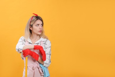 Young housewife with broom on yellow background. Space for text