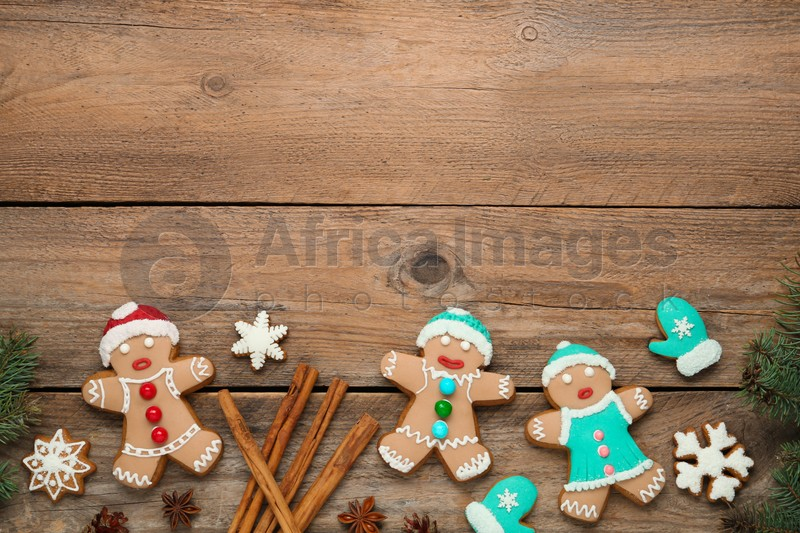 Delicious Christmas cookies, cinnamon and fir branches on wooden table, flat lay. Space for text