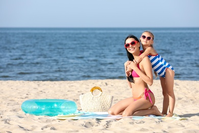 Happy mother and daughter on sandy beach near sea, space for text. Summer holidays with family