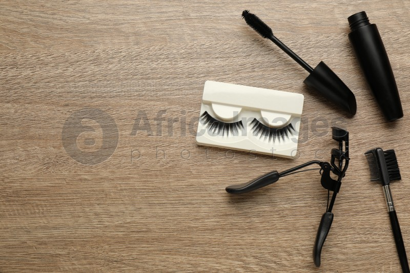 False eyelashes, curler, brush and mascara on wooden table, flat lay. Space for text