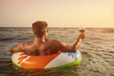 Man with glass of wine and inflatable ring resting in sea, back view