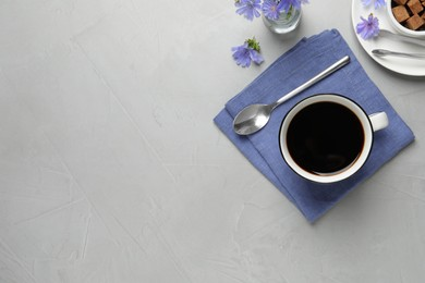 Cup of delicious chicory drink and flowers on light grey table, flat lay. Space for text