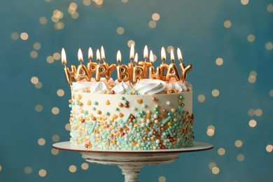 Beautiful birthday cake with burning candles on stand against festive lights