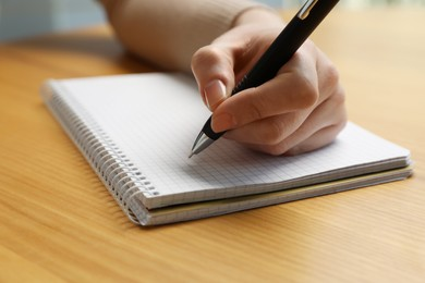 Left-handed woman writing in notebook at wooden desk, closeup