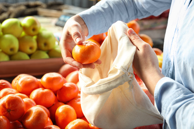 Woman putting tangerine into cotton eco bag at wholesale market, closeup. Life without plastic