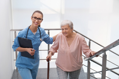 Doctor helping senior patient in modern hospital