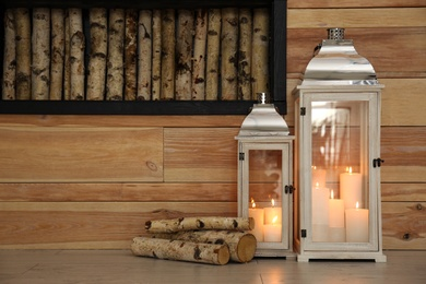 Decorative lanterns with candles on floor indoors, space for text. Interior elements