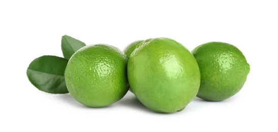 Fresh ripe limes with green leaves isolated on white