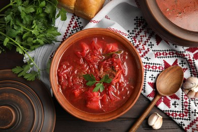 Stylish brown clay bowl with Ukrainian borsch served on wooden table, flat lay