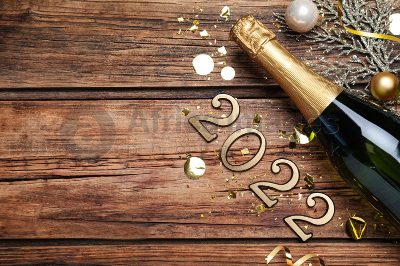 Happy New Year 2022! Flat lay composition with bottle of sparkling wine on wooden table, space for text