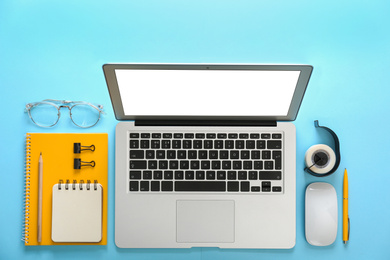 Laptop and office stationery on light blue background, flat lay