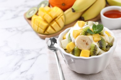 Delicious fruit salad on white marble table, space for text