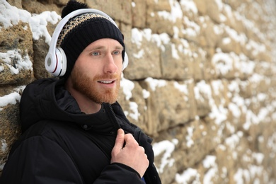 Young man listening to music with headphones near stone wall. Space for text