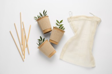 Paper cups with green twigs, mesh bag and bamboo straws on white background, flat lay. Eco friendly lifestyle