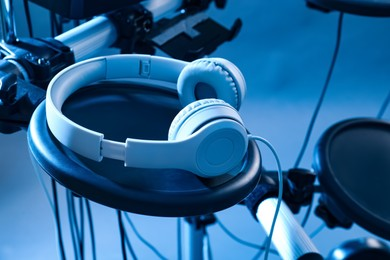 Modern electronic drum kit with headphones on light background, toned in blue. Musical instrument