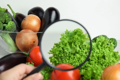 Woman with magnifying glass exploring vegetables, closeup. Poison detection