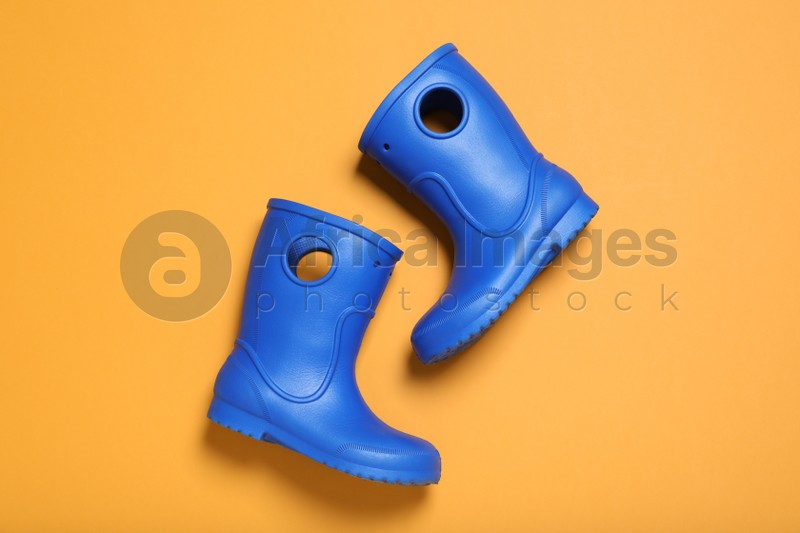 Bright blue rubber boots on orange background, top view