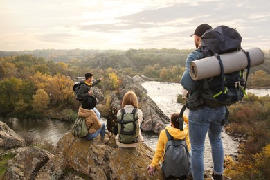 Group of friends with backpacks enjoying beautiful view near mountain river