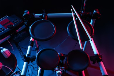 Modern electronic drum kit on dark background, color toned. Musical instrument
