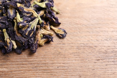 Pile of dry organic blue Anchan on wooden table, closeup with space for text. Herbal tea
