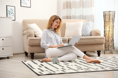 Pretty young woman with laptop sitting on floor at home