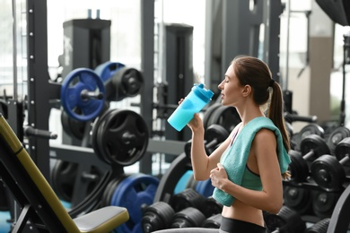 Athletic young woman drinking protein shake in gym