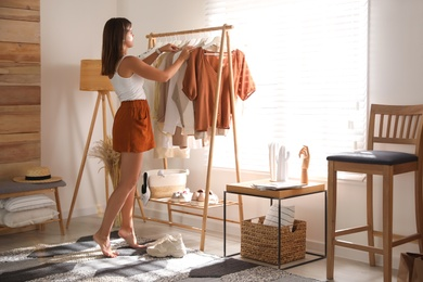 Young woman choosing outfit in dressing room