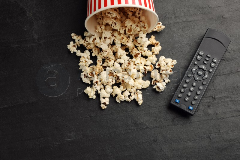 Modern tv remote control and popcorn on black table, flat lay