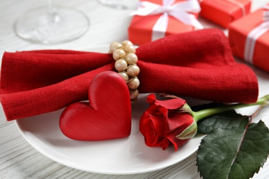 Beautiful place setting with decorative heart on white wooden table, closeup view. Valentine's day romantic dinner