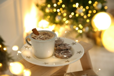 Tasty hot drink, cookies and Christmas lights in room